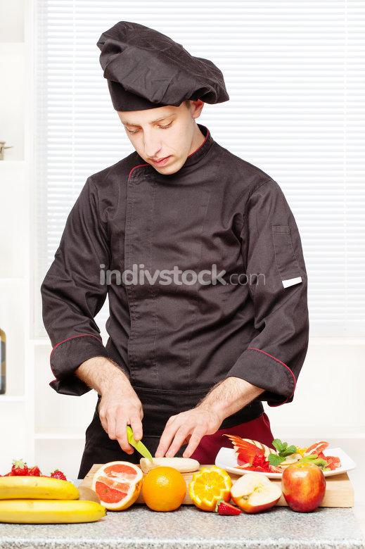 chef in black uniform cutting fruit