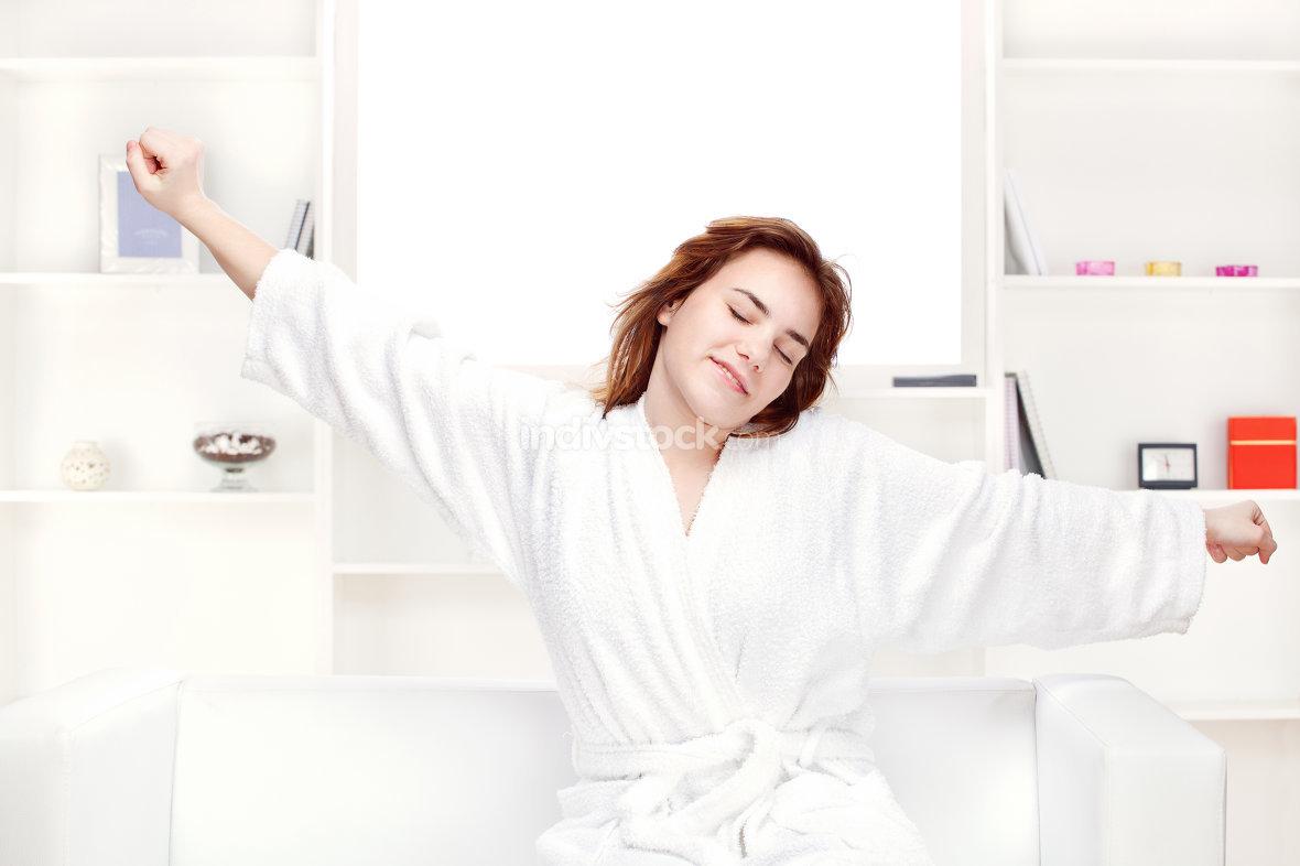 girl in bathrobe stretching arms