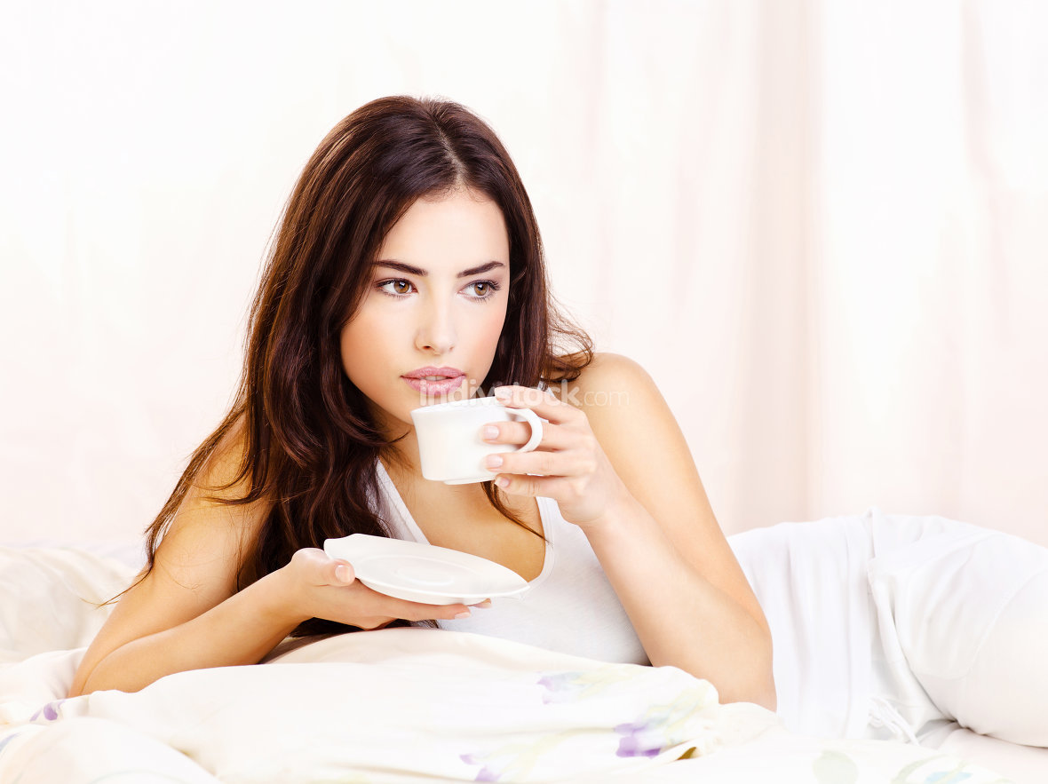 Pretty woman dink coffee in bed