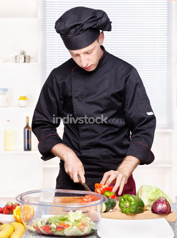 chef cutting bell peppers in kitchen