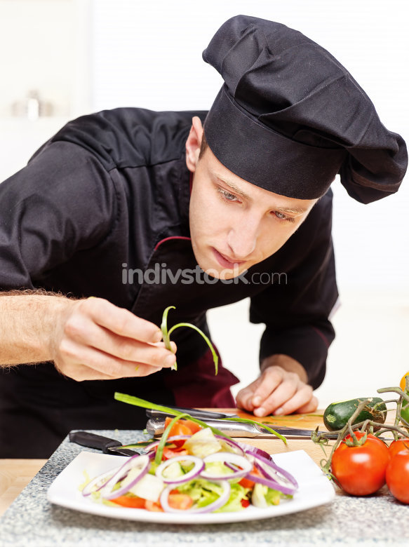chef decorating delicious salad plate