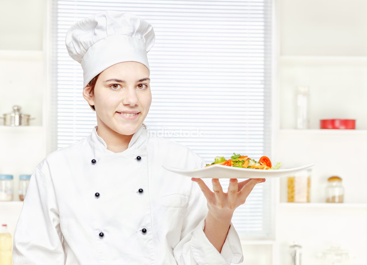 chef holding meal in kitchen