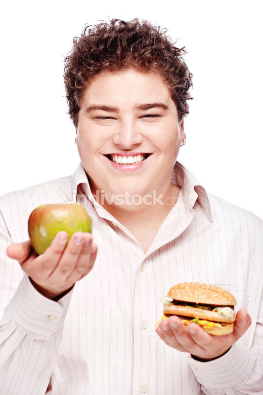 chubby man holding apple and hamburger