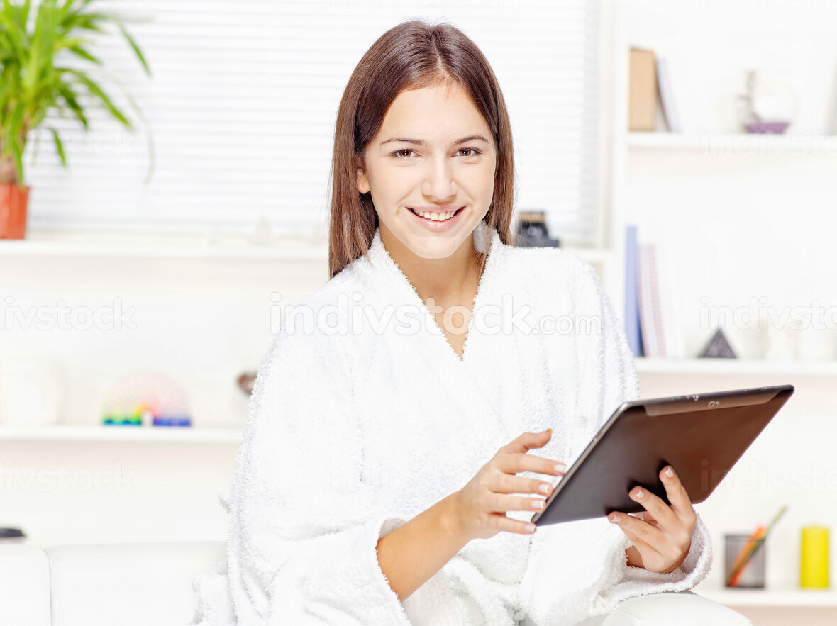 girl in bathrobe at home with touch pad
