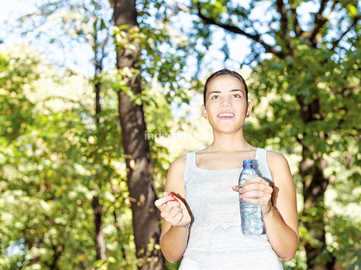girl in forest holding bottle of water