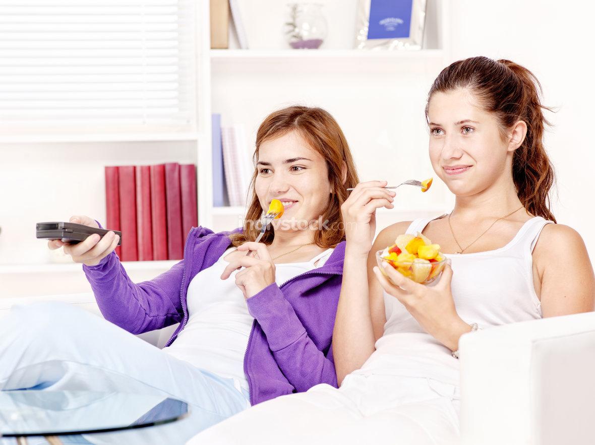 girls watching tv and eating fruit