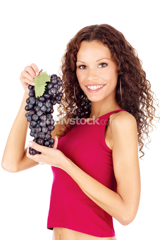Happy brunette holding grape