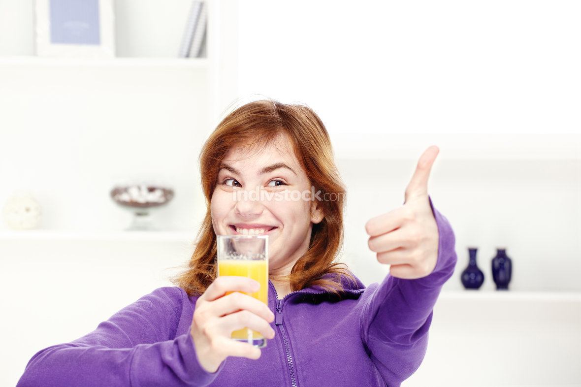 happy teenage girl drinks orange juice at home