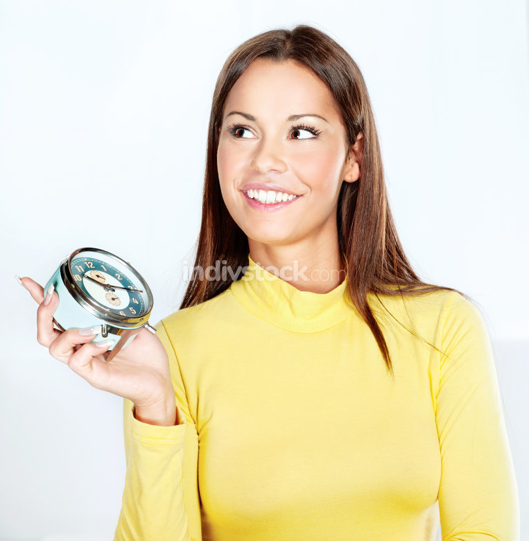 Happy woman holding alarm clock