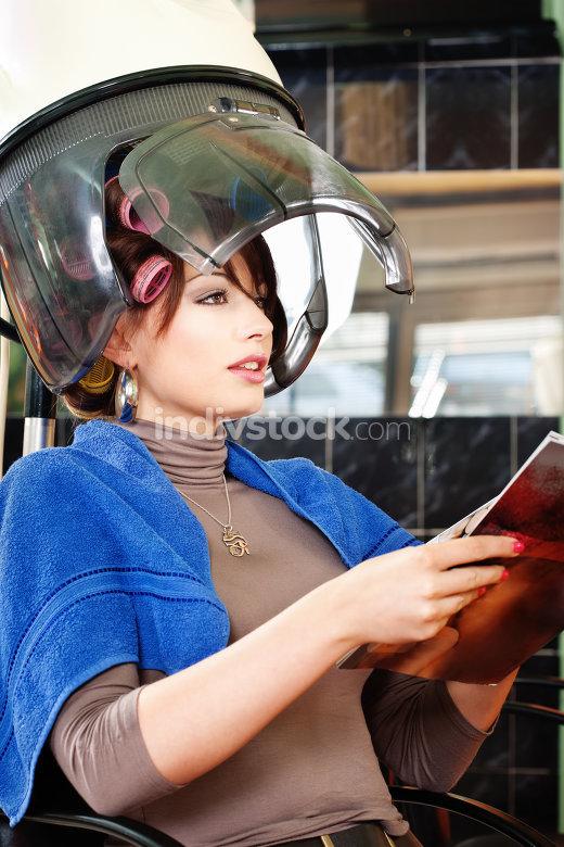 Pretty woman under bonnet hair dryer