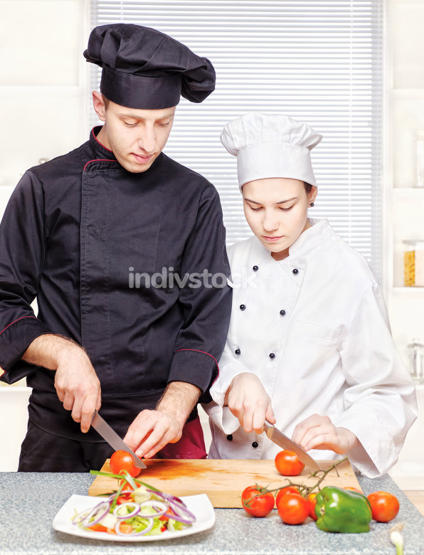 Senior chef teaches young chef to cut