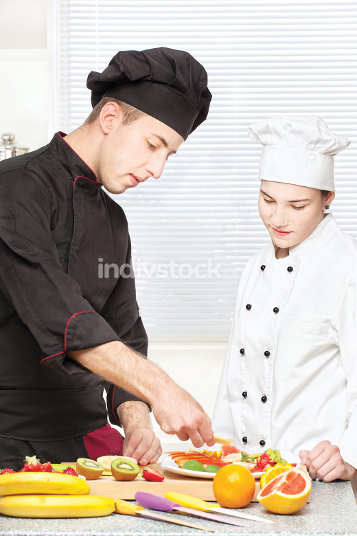 Senior chef teaches young chef to decorate