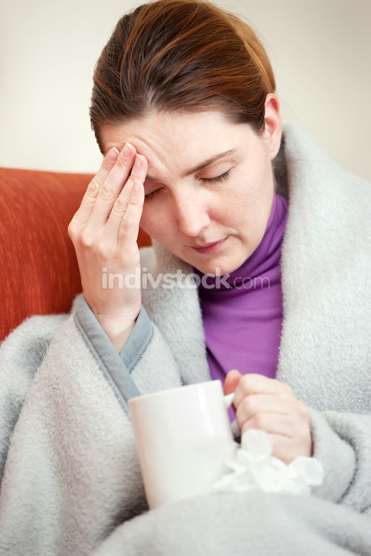 sick woman covered with blanket at home