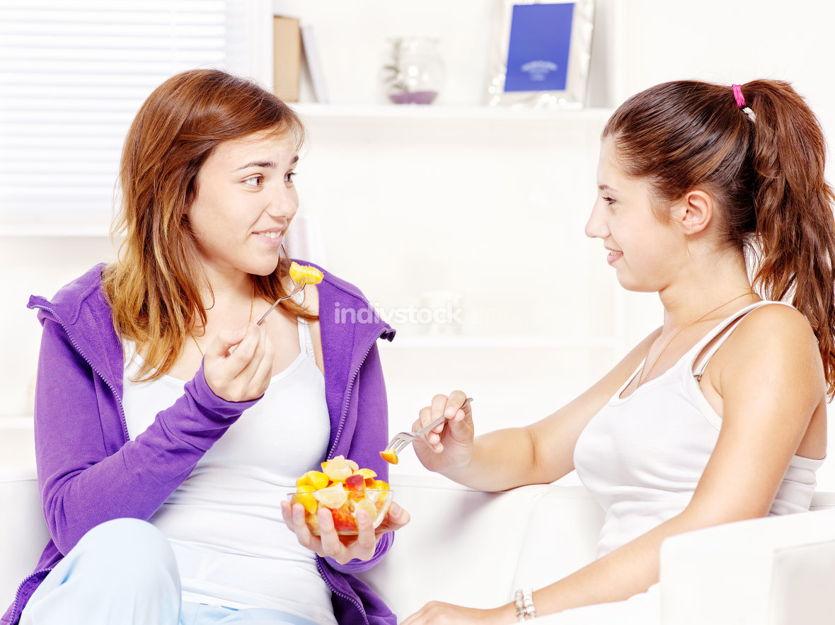 Teenage girls chating and eating fruit