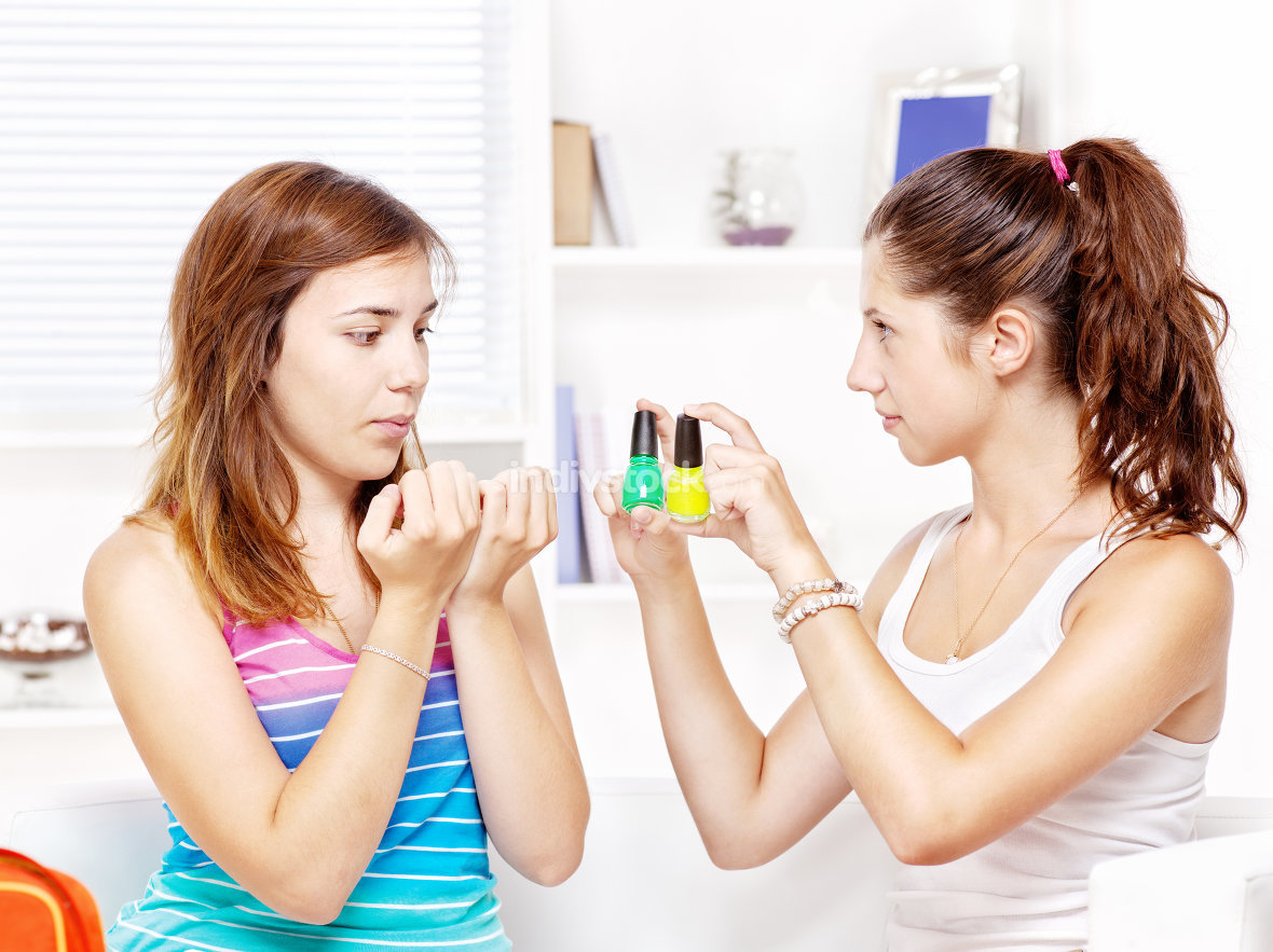 teenage girls polishing fingernails