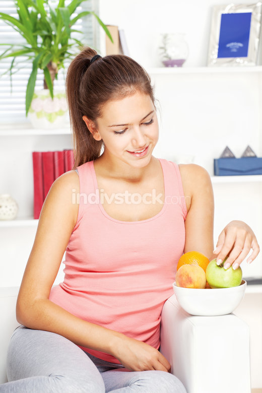 woman at home on sofa with fruits