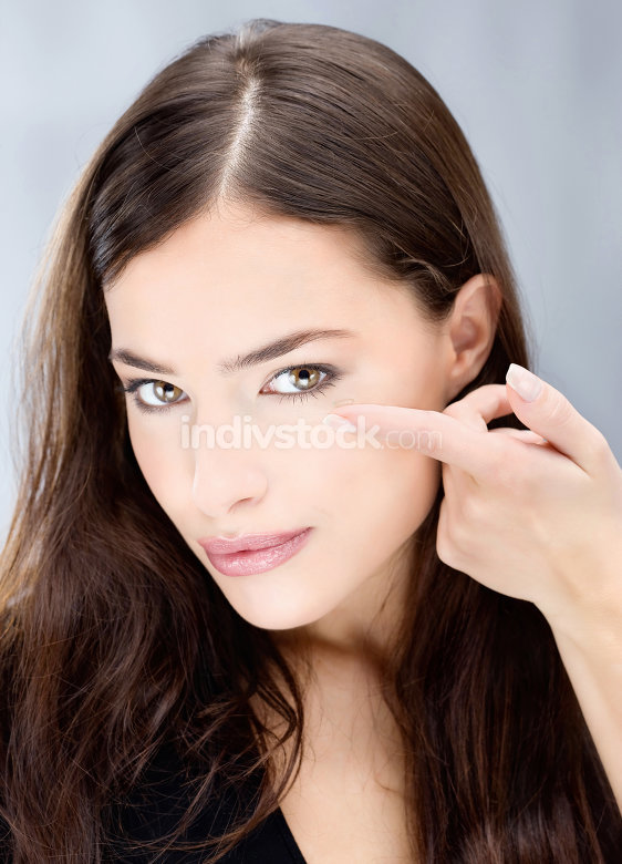 Woman hold conctact lens in front of eye