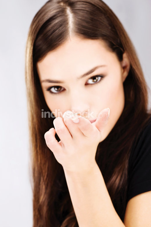woman holding contact lens on finger