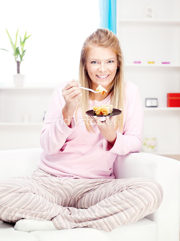woman on sofa eating cake at home