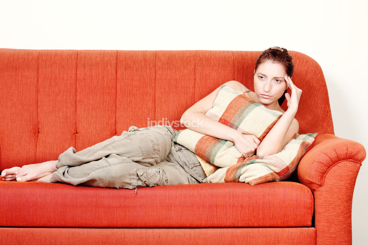 Woman with headache on sofa at home