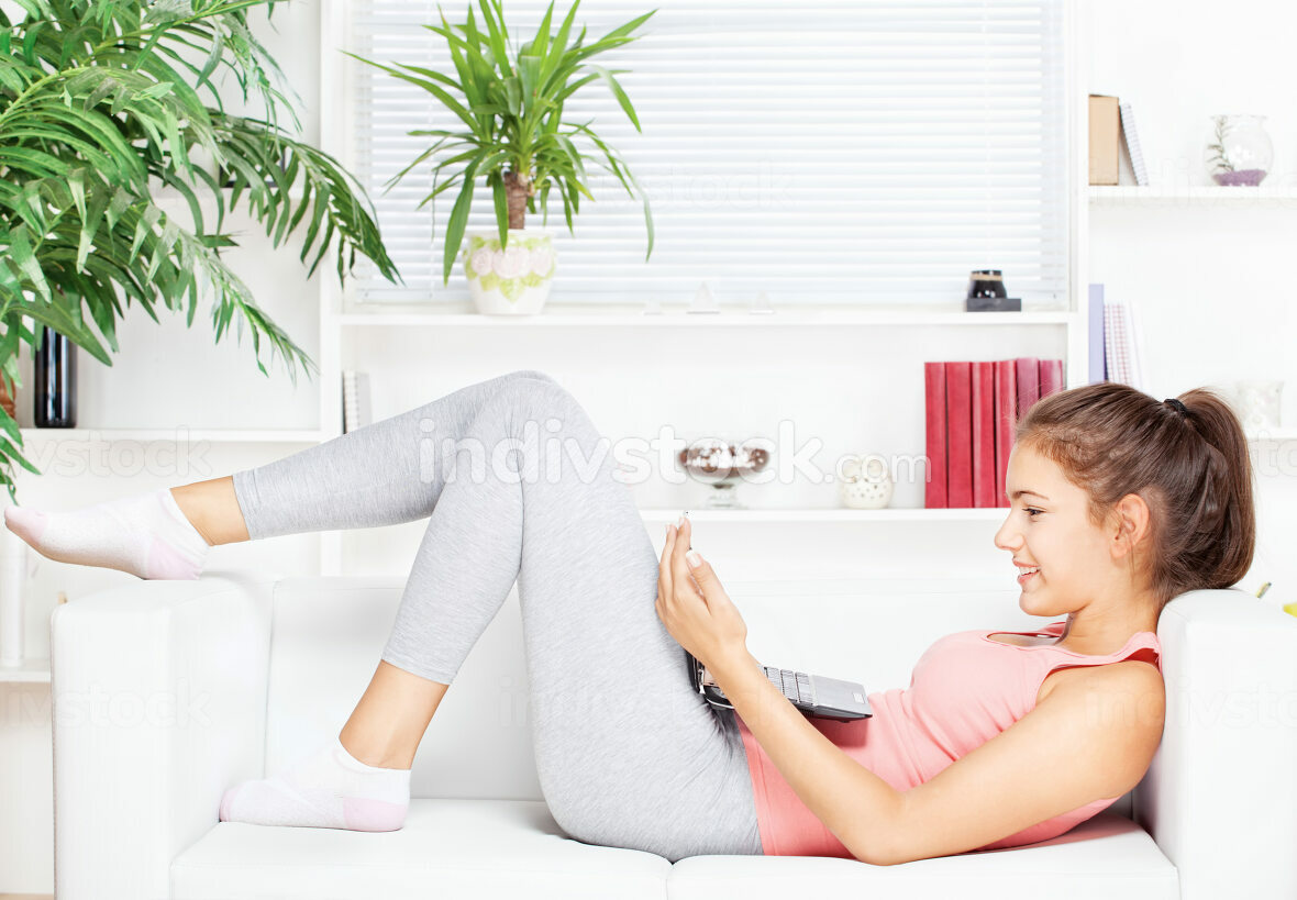 woman with laptop lying on sofa