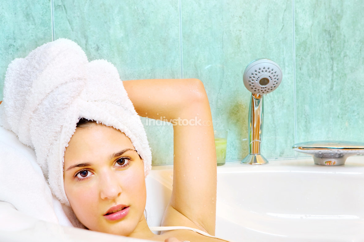 woman with towel on head in bathtub