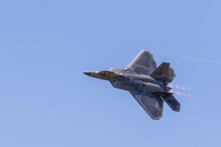 F-22 Raptor in flight with vapor clouds