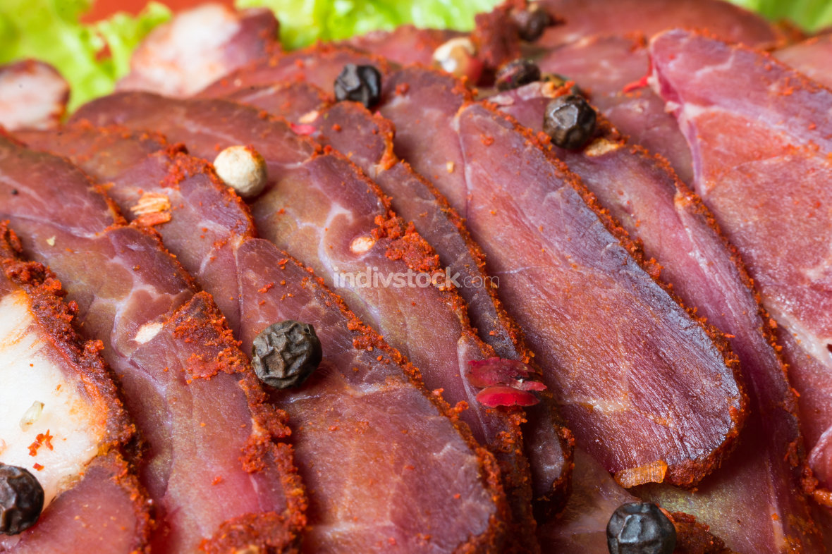 Cut pieces of smoked meat with lettuce and pepper