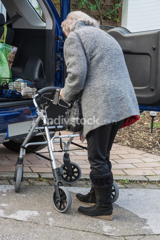 Elderly lady with a walker in front of a car.