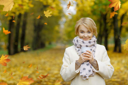 Beautifl blonde girl holding cup of hot tea in beautiful autumn
