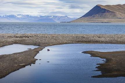 Beautiful scenic view of blue gulf under barren mountain range w