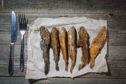 Dried fish with fork and knife on the table