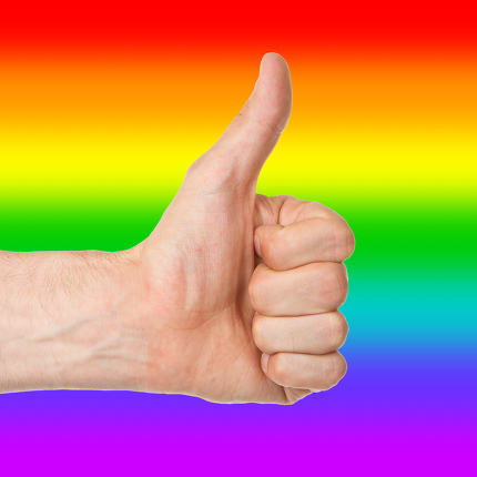 Image of a mans hand showing thumb up, rainbow flag