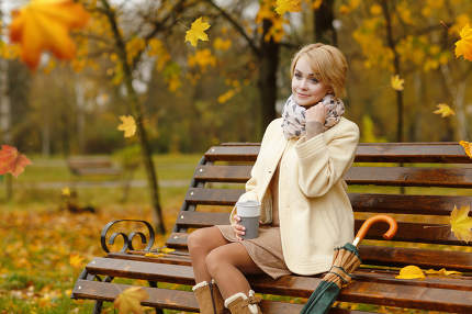 Lonely beautiful girl sitting in autumn park wooden bench