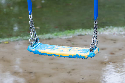 Plastic swing hanging over a puddle