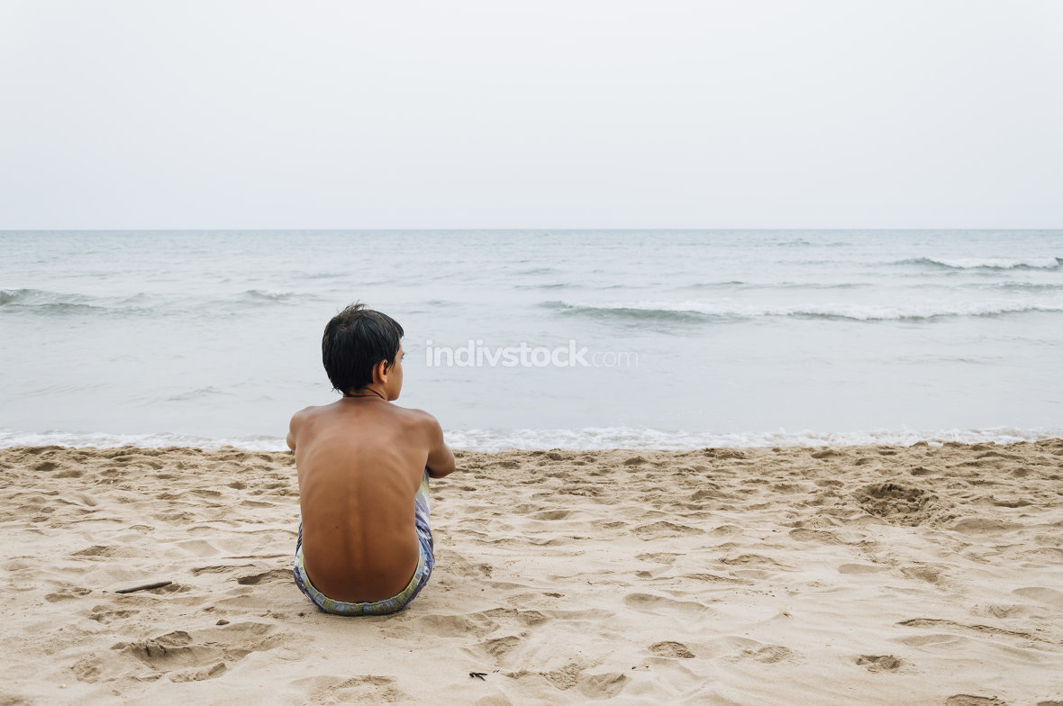 Boy sitting at the beach