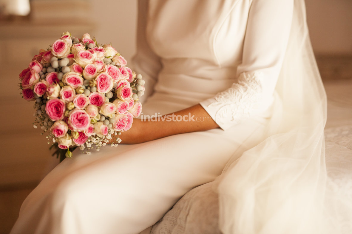 Bride sitting in the bed holding the bouquet in the white colore