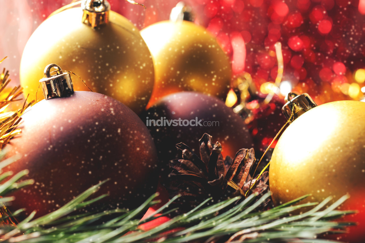 Christmas balls lying on spruce branches and falling snowflakes
