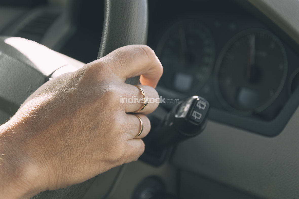 Close up of woman hand driving a car.