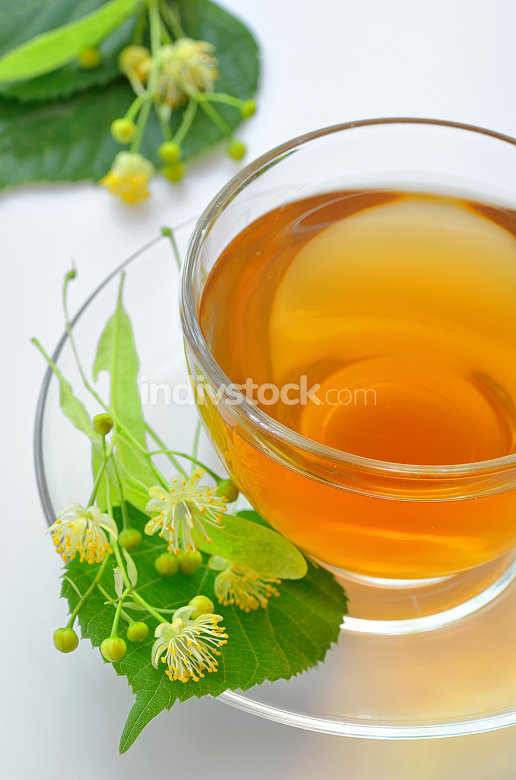 cup with linden tea and flowers