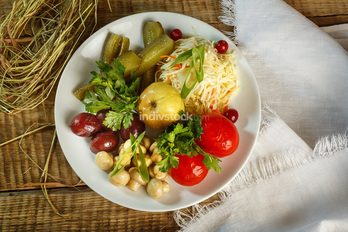 Different types of vegetables on white plate. Pickled cucumbers,
