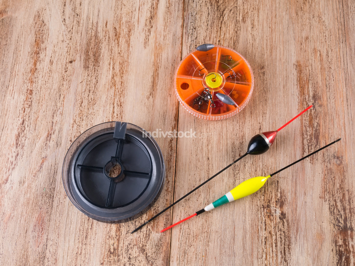 Floats, box for hooks and fishing line. Wooden background