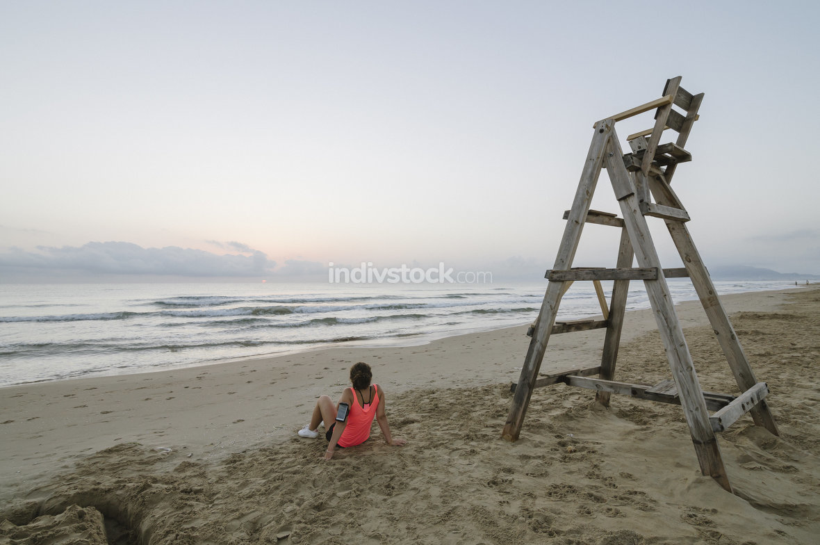 Girl on the beach watching the sunrise