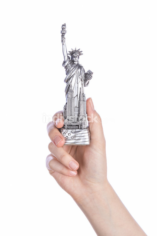 Hand holding a Statue of Liberty souvenir toy