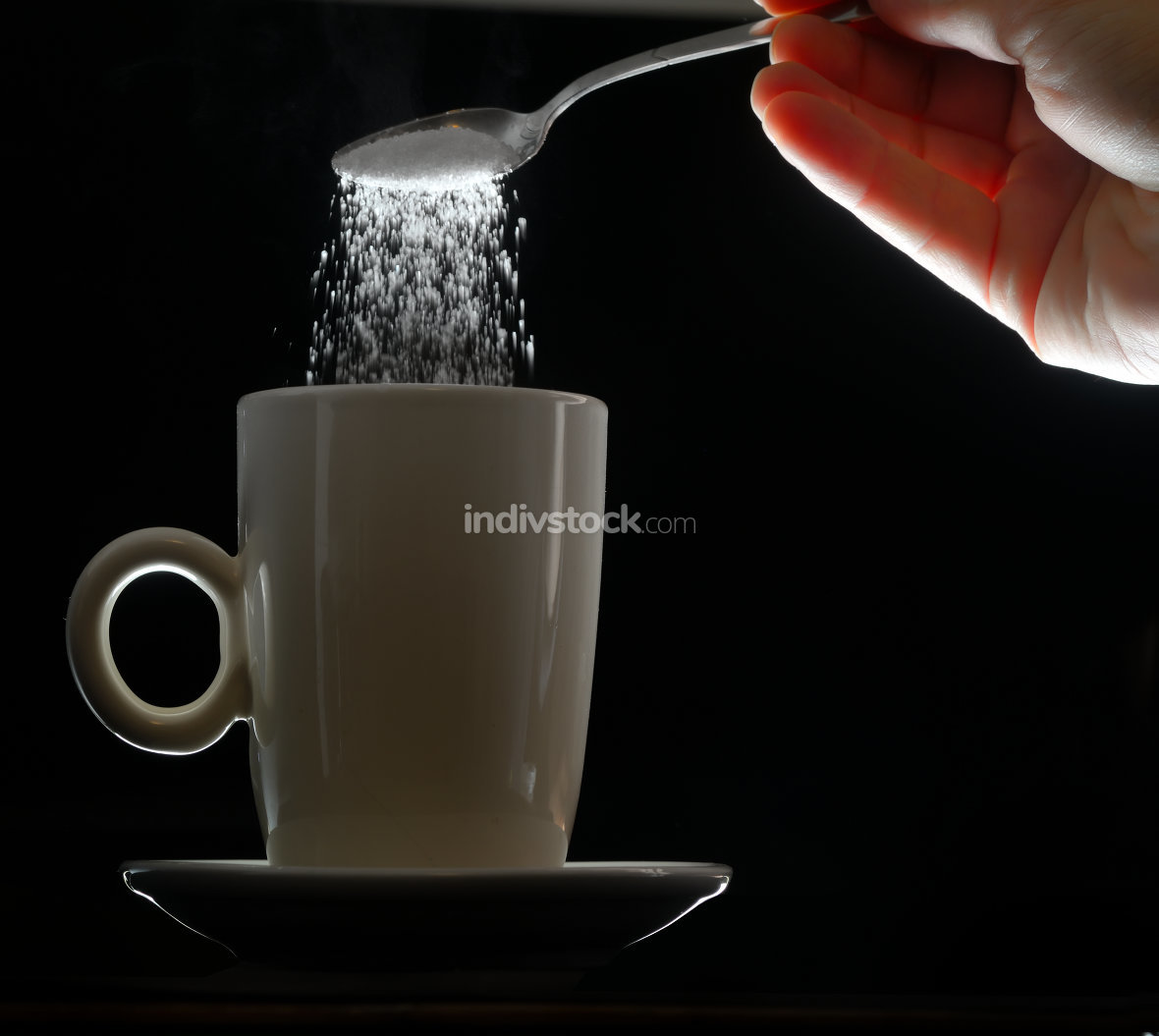hand pouring brown sugar in white cup