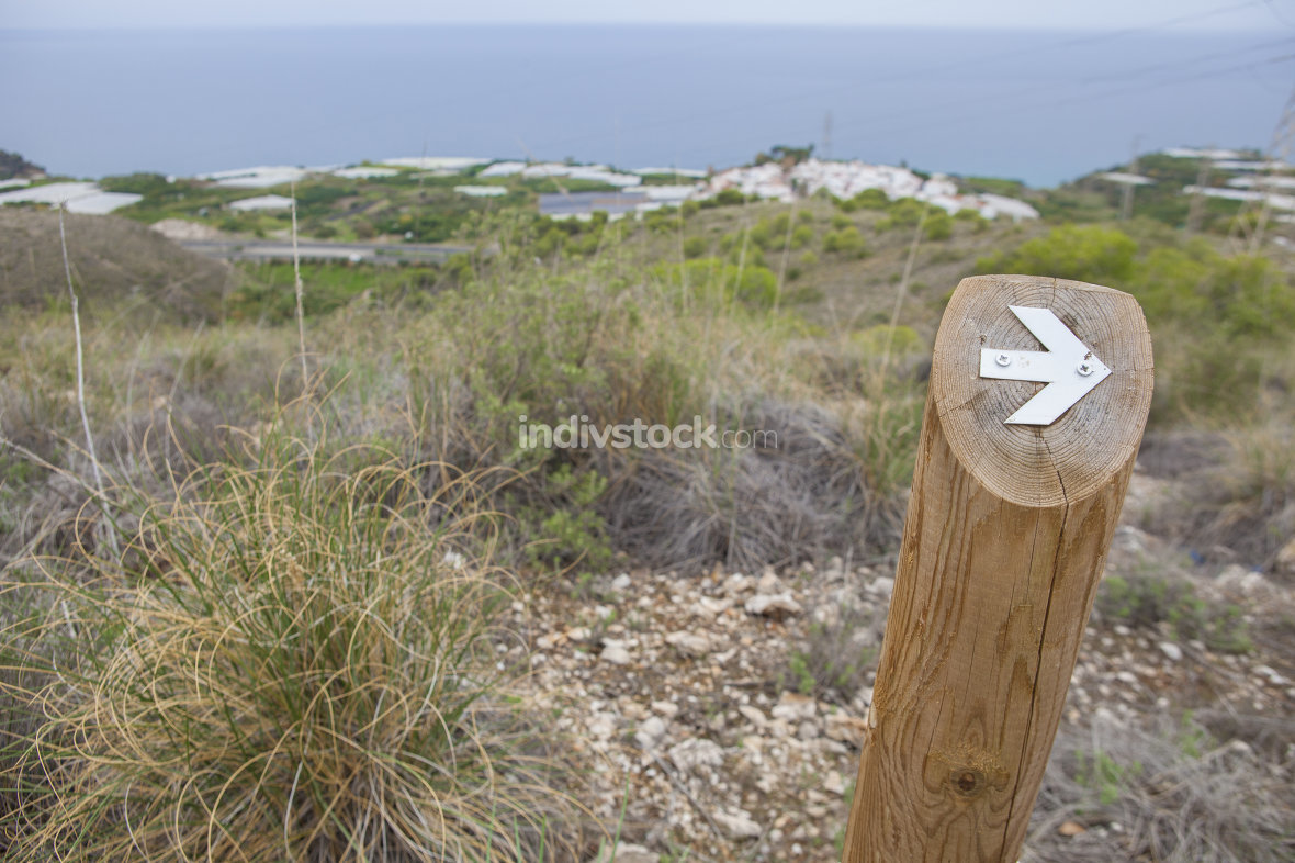 Hiking sign at trekking path beside the coast