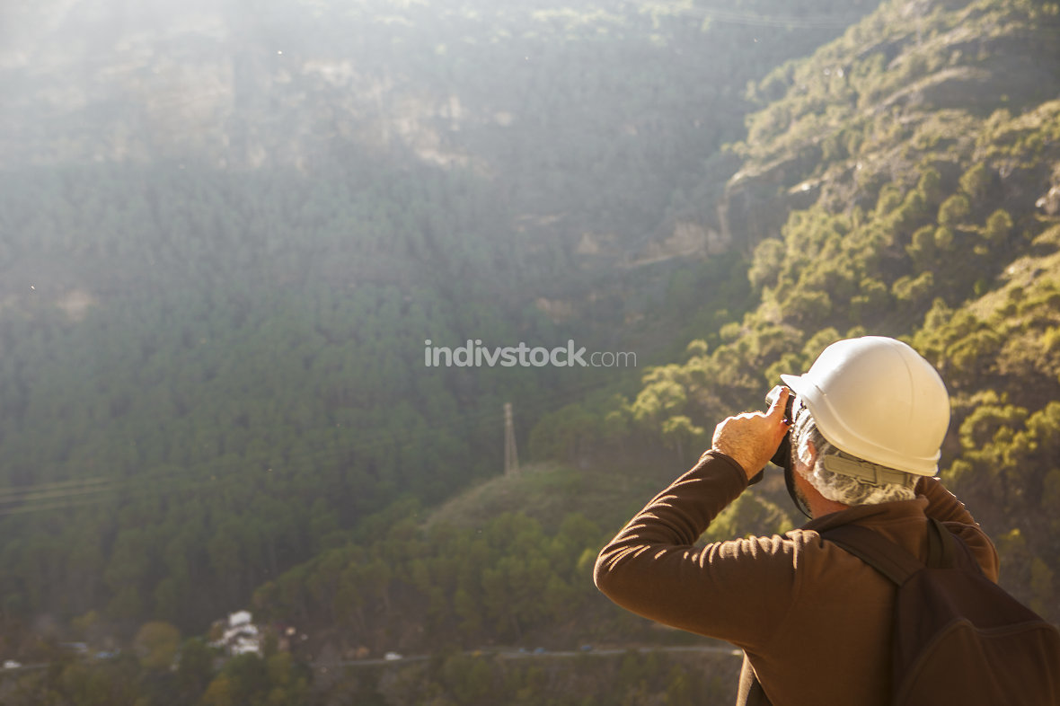 Mature man looking on binoculars on mountains
