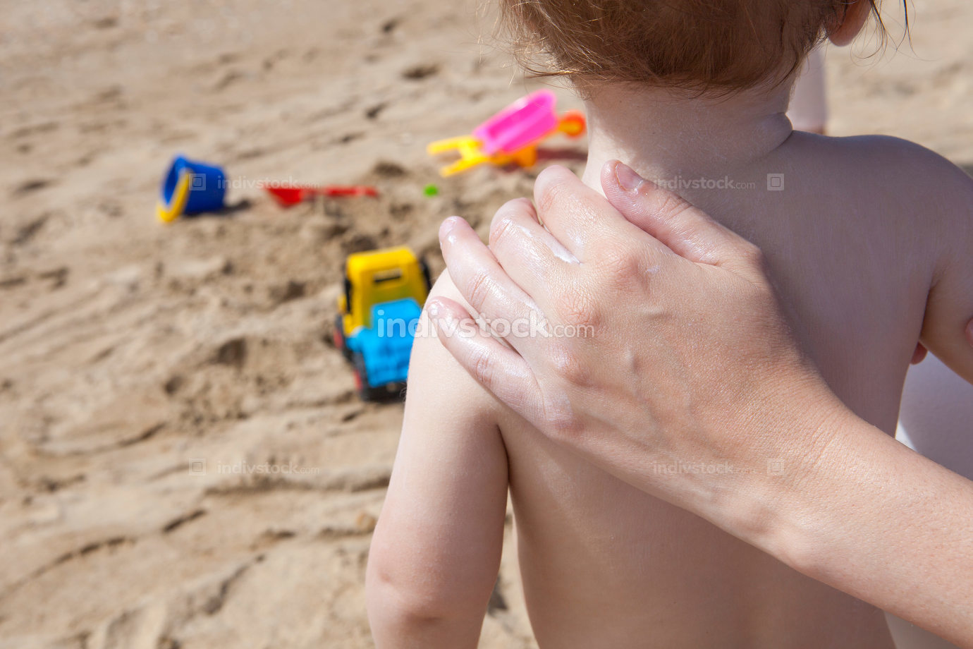 Mother applying sun cream to her baby on  back with beach toys a