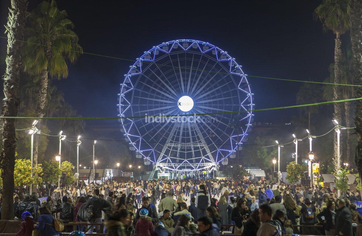 People enjoy visiting Christmas market with ferris wheel and ice
