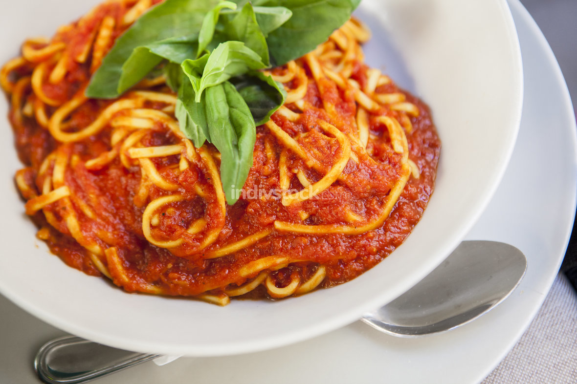 Plate of spaghetti bolognese with basil garnish